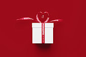 White Gift Box Tied By Happy Valentine's Day ( Alles Liebe Zum Valentinstag in German ) Printed Red Ribbon Sitting Over Red Background