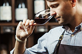Bokal of red wine on background, male sommelier appreciating drink