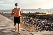 Young handsome man exercising and running near the ocean in the morning during quarantine.