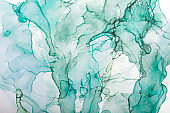 Watercolor alcohol ink swirls. Transparent waves in turquoise green colors. Delicate pastel spots. Digital decor
