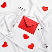 Romantic concept. Valentines day background. Red envelope, champagne glasses and hearts on white silk sheet
