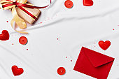 Romantic concept. Valentines day background. Red envelope, Gift box and hearts on white silk sheet