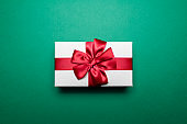 Close-up of white gift box with red ribbon bow on background of  green color.