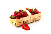 Fresh red strawberries in wooden basket on white background. Agriculture and ecological fruit farming concept.