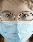 Portrait of a young girl in glasses and a medical mask close-up. Flu epidemic, dust allergy, protection against virus. Coronavirus pandemic.