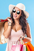 A woman in hat and sunglasses happily holding her bags after shopping.