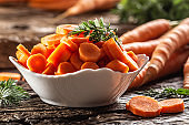 Sliced pieces of carrot in a bowl and a fresh bunch of carrots in the background.