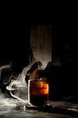 Old-fashioned glass of cold drink in dark bar with beautiful white smoke around