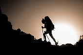 silhouette of woman tourist with trekking sticks and backpack who walks along rocky path