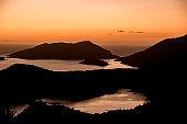 Amazing bright orange sunset over mediterranean sea and mountains.