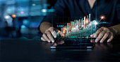 Businessman using tablet analyzing sales data and economic growth graph chart. Business planning and strategy. Analyzing trading of exchange. Financial and banking. Technology digital marketing.