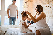 beautiful young adult woman straightens the hair of little cute girl sitting on the bed