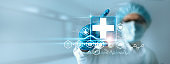 Medicine doctor holding medical cross icon with icon healthcare network connection on modern virtual interface on hospital background, Innovation and healthcare technology concept.
