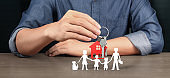 Real estate agent handing over house keys in hand, protecting paper chain family