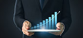Graph growth and increase of chart positive indicators in his business,tablet in hand