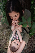 A little baby lies on the lap of her mother, who in turn kisses her daughter's sweet feet. Love, day and motherhood concept. Walking a happy family in the park with a small child. Close up portrait