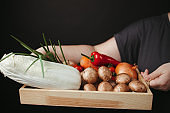 Woman holding box with vegetables and mushrooms