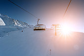 Ski lift empty ropeway on hilghland alpine mountain winter resort on bright sunny evening . Ski chairlift cable way with people enjoy skiing and snowboarding. Sunset sky backlit shining on background