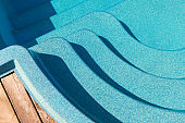 New modern fiberglass plastic swimming pool entrance step with clean fresh refreshing blue water on bright hot summer day at yard or resort hotel spa area. Wooden flooring deck of teak or larch board