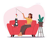 Love, Care of Animals, Woman and Pet Concept. Female Character and Cat Play with Toy Sitting on Couch in Living Room