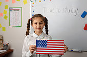 Little girl with flag of USA at the lesson of Country studying telling about the USA to schoolmates