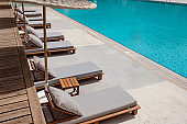 Wooden sunbeds with ratang umbrellas near swimming pool