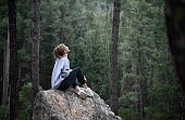 Woman in the forest sitting on the rock.