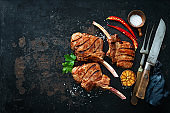 Grilled veal meat ribs cutlets with ingredients on rustic dark background