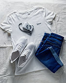 Composition of women's summer clothes - white t-shirt, denim shorts, white sneakers, white camera, top view