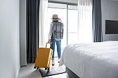 Tourist woman with luggage in hotel after check-in. Conceptual of travel and vacation.