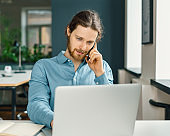 Young busy man entrepreneur talking on mobile phone in office
