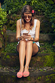 Caucasian young woman using modern smartphone in oriental garden.