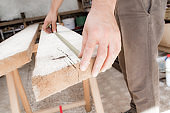 Male carpenter working with wood material in a garage.