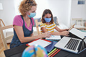 Child home studying education, homeschooling, with private tutor / mother with protective mask in the time of viruses, flu and seasonal pandemic.