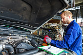 Male auto mechanic working at the repair shop.