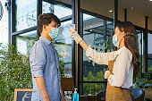 Asian woman cafe employee after take temperature Asian man with face mask before go to restaurant or coffee cafe for new normal lifestyle  coronavirus covid-19 pandemic.