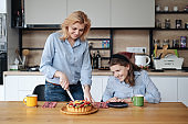 Mother and daughter eatting tasty berry cake with tea at home