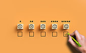 hand selecting a happy emoticon symbolizing a very good review