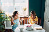 Women happy friends at home sitting and smiling with white birthday cake