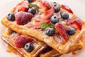 Belgian waffles with strawberries, blueberries and syrup, homemade healthy breakfast, selective focus