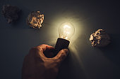 man hand bulb and crumpled paper