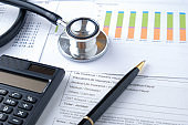 Stethoscope with Pen, Charts, Graphs, Finance, Account, Statistics, Investment, Analytic Research Data, Medical and Insurances Concept