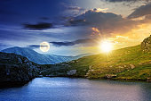 day and night change above the landscape with lake