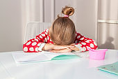 tired girl fell asleep on school exercise book, studying at home at her desk. child is doing homework. Hard task of reading and writing for elementary school