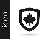 Black Canada flag on shield icon isolated on white background. Vector