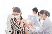 people getting covid vaccine in clinic or hospital. female wearing protective mask against covid-19. staff medical and Nurses using syringe to inject vaccine to arm body.