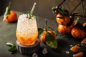 Fresh cocktail with crushed ice, rosemary and tangerines