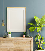 Mockup frame on cabinet in living room interior on empty dark blue wall background.