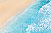 Travel and vacation image. Beach. Seascape. Coast as a background from top view. Blue water background from air. Strong waves.