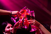 Group of people toast drinks at party in dancing club